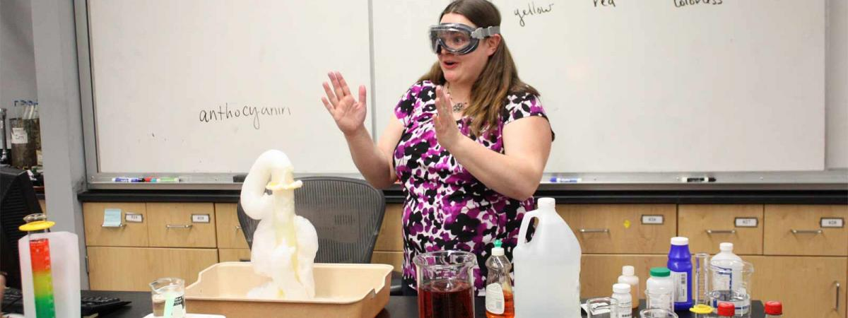 student wearing goggles giving a class demonstration in Chemistry at Minneapolis College