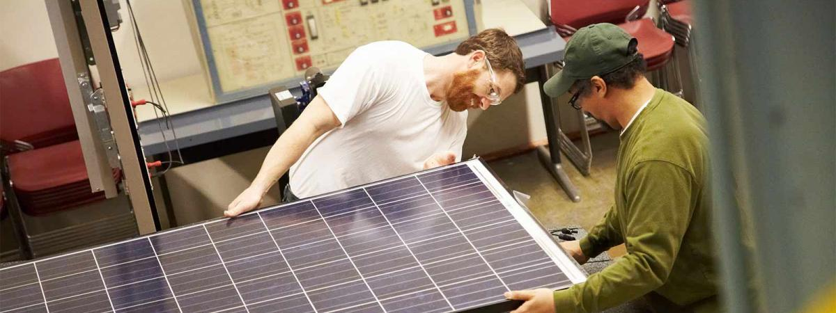 Two workers putting together a solar panel at Minneapolis College