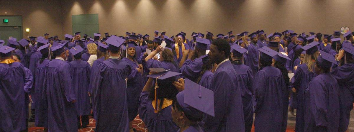 Students with their graduation gowns on waiting to line up and graduate