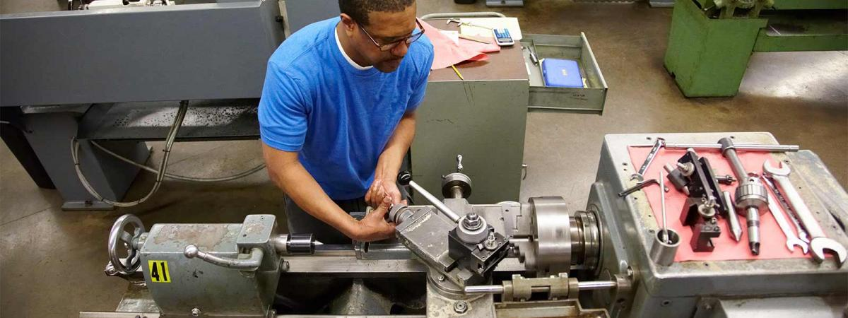 Student working a lathe in a machine shop