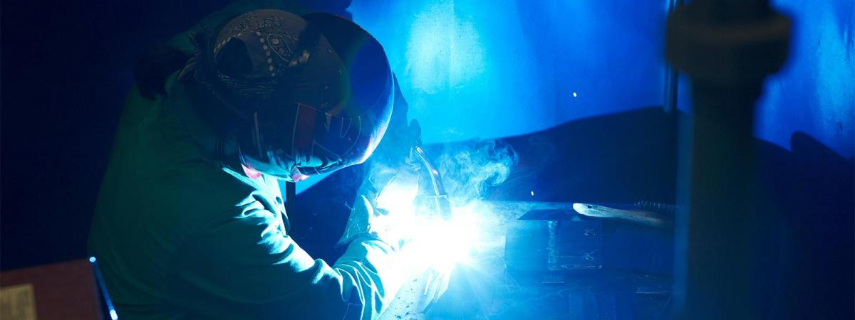 Student wearing welding mask performing a welding project
