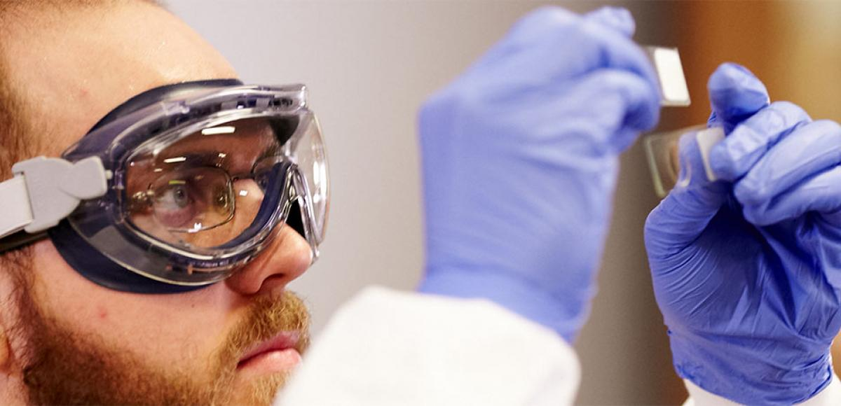Student wearing gloves and goggles analyzing lab results at Minneapolis College
