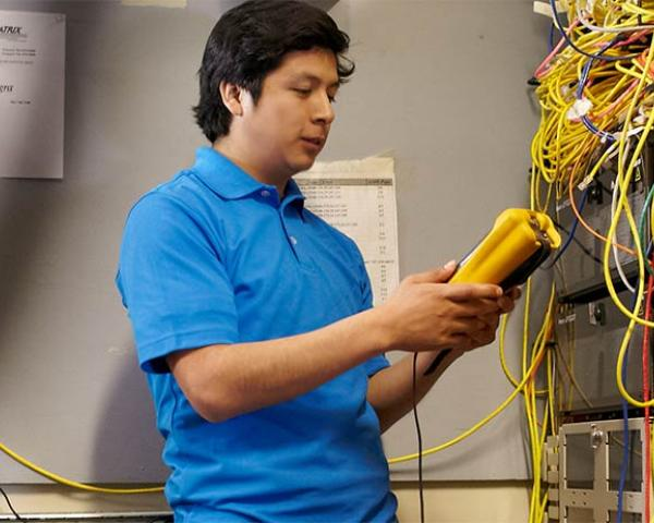 Student performing maintenance in the server room at Minneapolis College