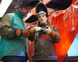 instructor showing student welding solution with student working in the background