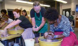 Instructor showing student how to spin pottery at Minneapolis College